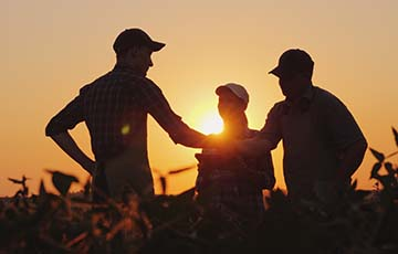 Three people in a field of crops